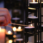 Hands light a candle at a station like those set up during worship at CRCC